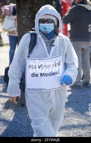 Chur, Schweiz. 6. März. Teilnehmer mit Transparent das Virus sind die Medien während der Demonstration gegen Corona Massnahmen in Chur. Stock Photo