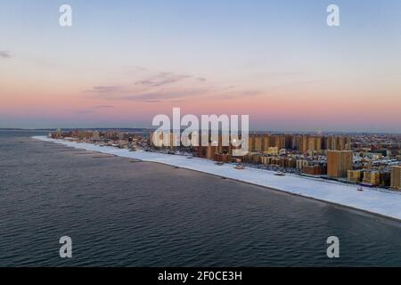 Aerial view of a snow covered Coney Island Beach during the winter at sunrise in Brooklyn, New York.