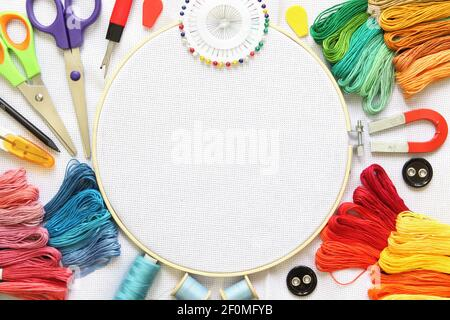 Embroidery hoop and multicolored accessories on white linen canvas with spools of thread, needle and scissors.