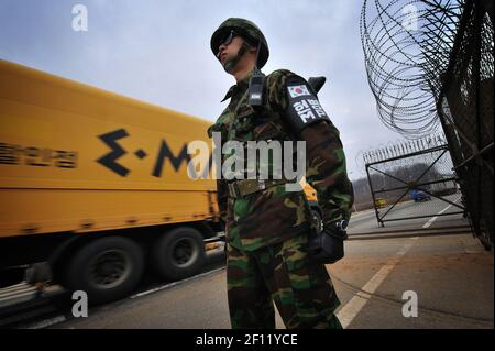 6 March 2009 - Paju, South Korea - A South Korean soldier stands guard as South Korean cars leave to the inter-Korean Kaesong Industrial Complex in North Korea through the last gate from South Korea, just south of the demilitarized zone (DMZ) separating the two Koreas. (Photo by Kish Kim/Sipa USA)