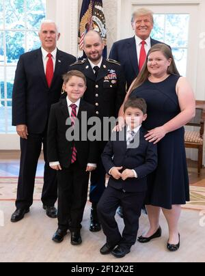President Donald Trump and Vice President Mike Pence pose for a photo with Medal of Honor recipient retired U.S. Army Staff Sgt. Ronald J. Shurer II his wife Miranda and sons Monday Oct. 1 2018 in the Oval Office