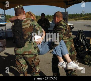 -- NO MAGS, NO SALES UNTIL 11/10/05 -- KRT US NEWS STORY SLUGGED: WEA-WILMA KRT PHOTOGRAPH BY TIM CHAPMAN/MIAMI HERALD (SOUTH FLORIDA SUN-SENTINEL AND ORLANDO SENTINEL OUT) (October 26) MIAMI, FL -- Members of the Florida National Guard help volunteer Kathy Leahy to an aid station after she was hit by the tailgate of a truck getting ice at a distribution center for Hurricane Wilma victims at Metro Zoo in Miami, Florida, Wednesday, October 26, 2005. She was treated at the scene by the guard and fire rescue. (Photo by cdm) 2005