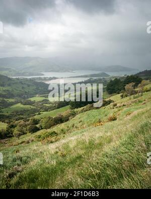 Storm approaching a valley with green rolling hills, portrait shot made on Banks Peninsula near Christchurch, New Zealand