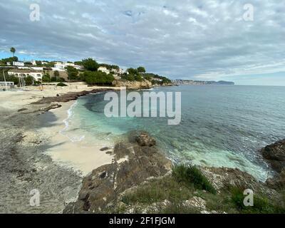 Sea waves lash line impact rock on the beach, located in Alicante, Spain,