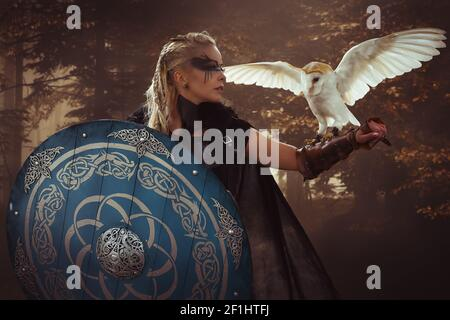 Warrior, beautiful white owl, Viking blonde woman with shield and sword, braids in her hair. Stock Photo