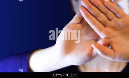 Teenage girl keeps her hands crossed in front of her face, to protect herself from a stranger, ideal