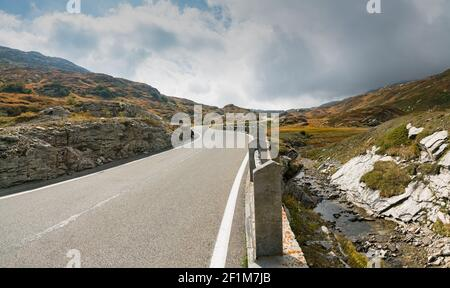 Two-lane road leading over a high remote and wild mountain pass in the Swiss Alps