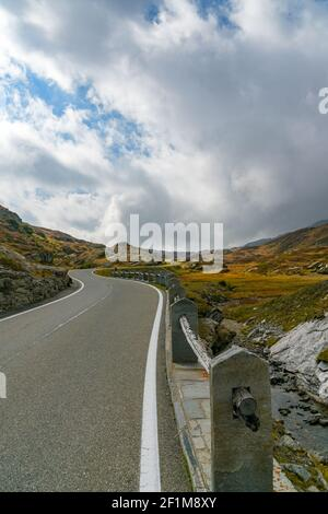 Vertical view of a two-lane road leading over a high remote and wild mountain pass in the Swiss Alps