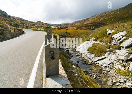 Two-lane road leading over a high remote and wild mountain pass in the Swiss Alps in autumn