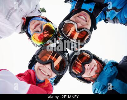 Close up of happy friends skiers in ski glasses touching heads and expressing positive emotions. Group of joyful people wearing ski helmets and goggles. Concept of friendship and skiing.