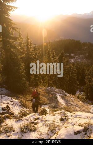 Backpacker hikes up mountain ridge during sunet.