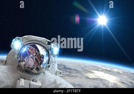Astronaut in outer space over of the Earth.  Elements of this image furnished by NASA