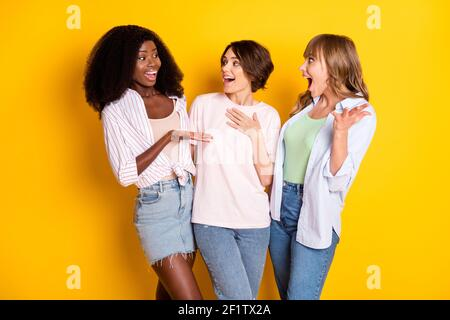 Portrait of three attractive cheerful girls talking having fun gossiping embracing isolated over bright yellow color background