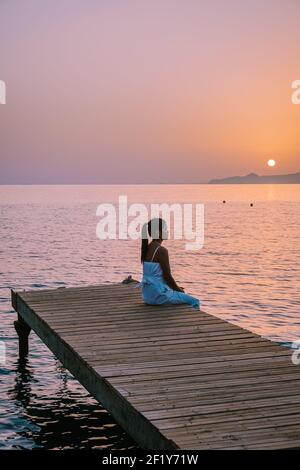 Crete Greece, young romantic couple in love is sitting and hugging on wooden pier at the beach in sunrise time with golden sky.