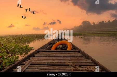 Scenic river sunset with rural landscape as viewed from a fishing boat. Photograph shot at Burdwan district in West Bengal, India - Stock Photo