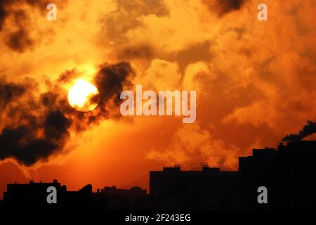 Sunrise on colorful dramatic sky, orange sun shining through dark clouds above the buildings silhouettes. Picturesque city landscape for horror