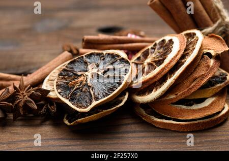 Cinnamon sticks and dry orange slices on brown wooden board Stock Photo
