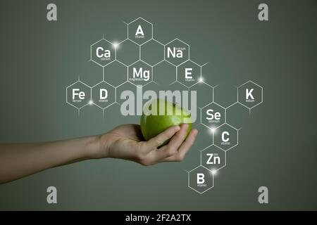 Woman`s hand holding green apple, microelement icons in molecular hexagons on grey background. Weight Loss concept template for product design.