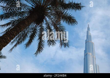 DUBAI, UNITED ARAB EMIRATES - FEBRUARY 10, 2021: Bottom-up view of Burj Khalifa in contrast with the blue sky and clouds. At the bottom of the buildin Stock Photo