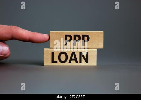 PPP, paycheck protection program loan symbol. Concept words PPP, paycheck protection program loan on wooden blocks on a beautiful grey backgrounds. Bu