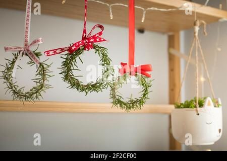 Three rosemary wreaths decorated with red festive ribbons, hanging from a shelf. Natural home decor, diy, idea for Christmas.