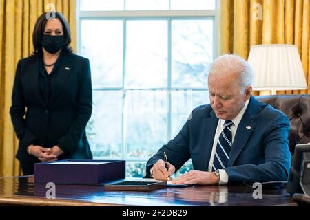 Washington, United States Of America. 11th Mar, 2021. U.S President Joe Biden signs the American Rescue Plan into law as Vice President Kamala Harris looks on in the Oval Office the White House March 11, 2021 in Washington, DC Credit: Planetpix/Alamy Live News Stock Photo