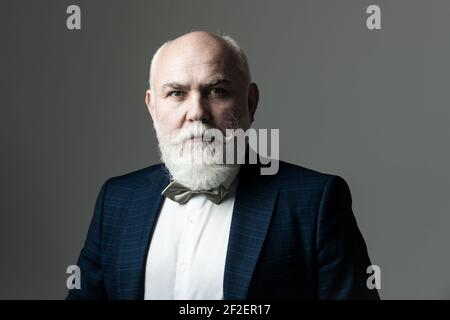 Portrait of a bearded middle-aged man over a gray studio background with copyspace. Serious Senior Man.