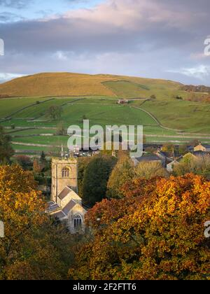 St. Wilfrid's Church is visible amongst the rich tones of autumn foliage in the quaint village of Burnsall, Yorkshire Dales National Park.
