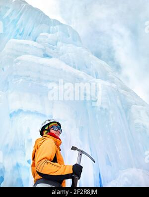 Woman climber in orange jacket with ice axe near frozen waterfall in the mountains