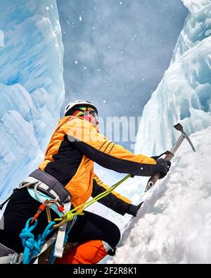Woman is climbing frozen waterfall with ice axe in orange jacket in the mountains