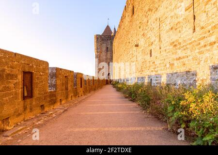 Wide fortified walls with walkways and arches of medieval castle of Carcassonne town at sunset