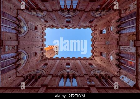 Wide angle view from the courtyard of Palazzo Pubblico to the famous Torre del Mangia. Siena, Tuscany, Italy