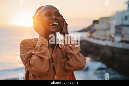 Happy senior African woman enjoying listening music in front of sea during summer sunset