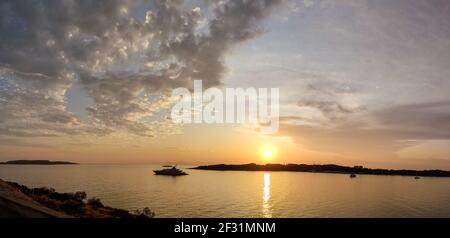 Orange sunset sun shining above Greek islands in Aegean sea. Panorama near Athens in Greece. Summer tourism travel. Scenic clouds and yacht in calm se