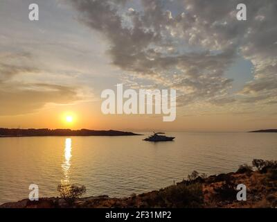 Orange sunset sun shining above Greek islands in Aegean sea in Greece. Summer tourism travel. Scenic clouds and yacht in calm sea in evening