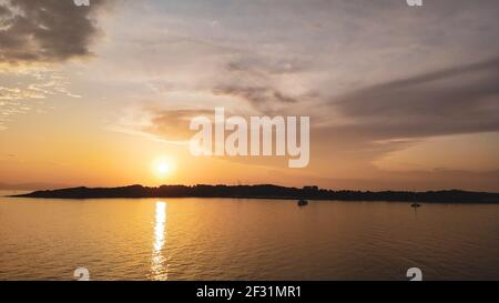 Orange sunset sun shining above Greek islands in Aegean sea near Athens in Greece. Summer tourism travel. Scenic clouds and yachts in calm sea in even