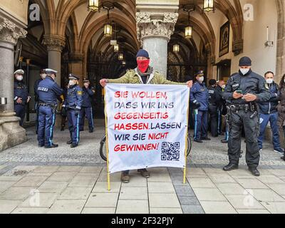Munich, Bavaria, Germany. 14th Mar, 2021. A Corona denier stands in front of Munich's Rathaus and police. Using the occasion of Germany going into a period of anti-Corona measures approximately one year ago, Corona deniers and anti-maskers led by Querdenken's Markus Haintz assembled at Munich's Marienplatz and then at the Maxmonument in an effort to protest against the Bavarian Landtag and promote their initiative to dissolve it and install a provisional government, presumably made of right-extremists, conspiracy theorists, QAnons, Libertarians, and anti-maskers. The group is