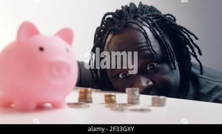 Man counting his savings. Close up of piggybank surrounded by coins. Investing decision. High quality photo
