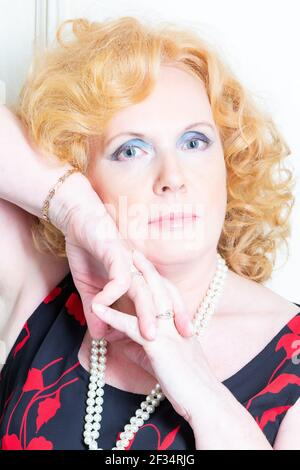 Beautiful mature woman posing. Red hair, white skin. Close-up, white background.
