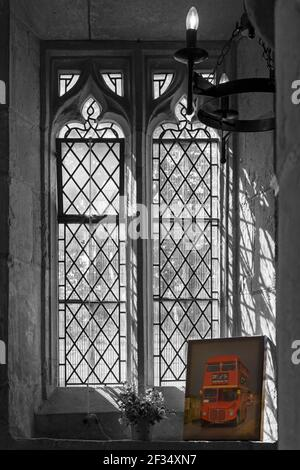 Lead light windows and picture of old red bus inside St Giles Church on Open Day, Imberbus event at Imber, Salisbury Plain, Wiltshire UK in August - Stock Photo