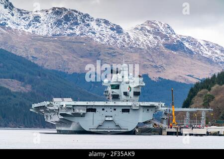 Finnart, Scotland, UK. 15 March 2021. Royal Navy aircraft carrier HMS Queen Elizabeth berthed on Long Loch  at Glenmallan to take on supplies and munitions ahead of naval exercises part of UK Carrier Strike Group 2021.  Iain Masterton/Alamy Live News Stock Photo