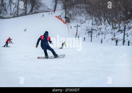 Down slope on snow covered mountain. Back view of snowboarder riding on slope, blurred selective focus. Winter sport and recreation - Stock Photo