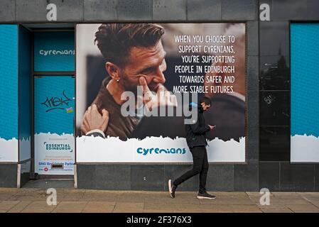 TYoung man looking at his phone as he walks by an advert for the Cyrenians on an empty shop on Princes Street, Edinburgh, Scotland, UK. - Stock Photo
