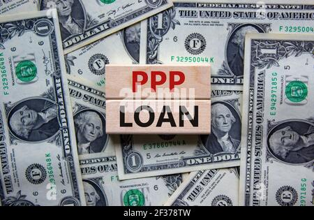 PPP, paycheck protection program loan symbol. Concept words PPP, paycheck protection program loan on wooden blocks on a beautiful background from doll