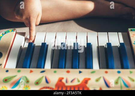 Caucasian kid is sitting on the floor playing the piano toy with one finger