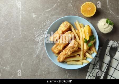 Concept of tasty eating with fried fish and chips on gray textured table