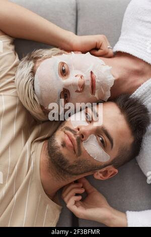 Top view closeup of young gay couple looking at camera while lying on couch together and wearing face masks, beauty and skincare concept