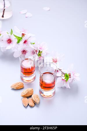 almond liquor. The traditional strong drink in italy to complete the dinner is a liqueur made from nuts and berries. Ratafia, alcohol in shot. on the table and a branch of blooming almonds. Copy space