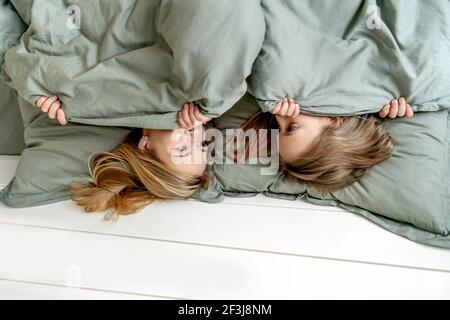 Woman with little girl hides under blanket. Morning, mother and daughter have a fun. Focus on womans eyes.