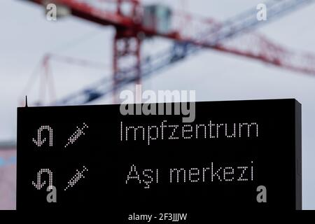 Cologne, Germany. 17th Mar, 2021. Cranes can be seen on a construction site behind a signboard in German and Turkish script, on the way to the vaccination centre. The infection figures are rising, at the same time planned vaccinations with the Astrazeneca vaccine are cancelled. Credit: Rolf Vennenbernd/dpa/Alamy Live News Stock Photo